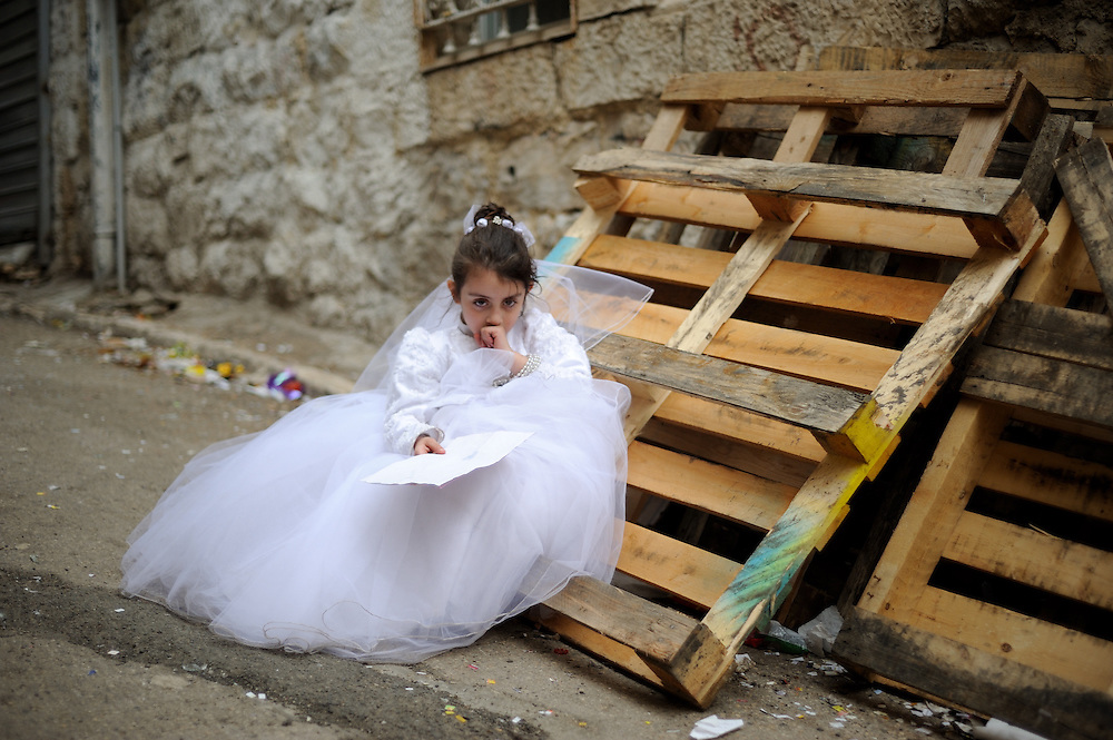 JERUSALEM, ISRAEL - MARCH 17, 2014: An Ultra-Orthodox Jewish girl, wearing a bride costume, is sitting in a street during Purim holiday in the ultra-orthodox Mea Shearim neighborhood in Jerusalem on March 17, 2014. The festival of Purim commemorates the rescue of Jews from a genocide in ancient Persia. Photo by Gili Yaari