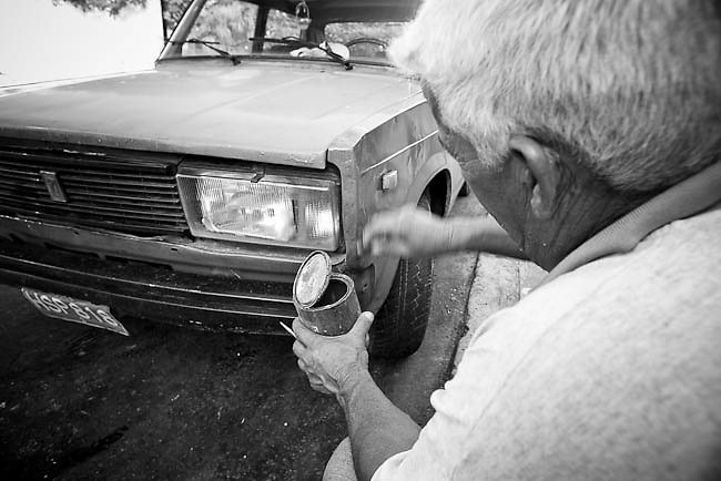 America, Cuba, Havana.  A man paint his car outside of his house . -04.07.2008, DIGITAL PHOTO, 49MB, copyright: Alex Espinosa/Gruppe28.