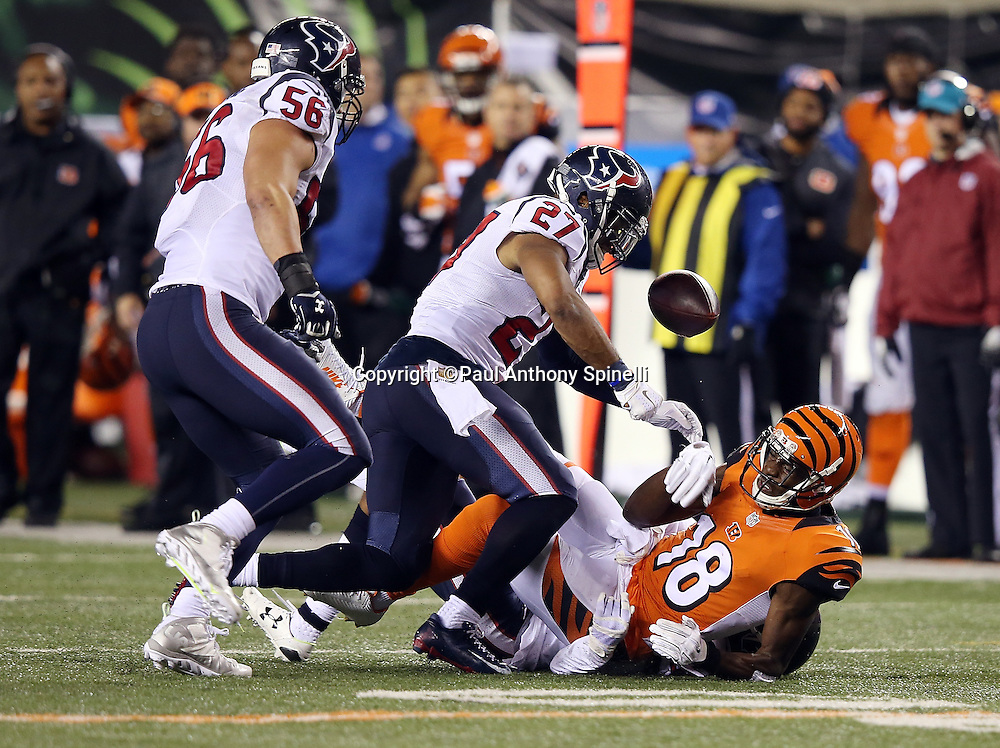 Cincinnati Bengals wide receiver A.J. Green (18) gets tackled by Houston Texans strong safety Kevin Johnson (30) as he catches a fourth quarter pass for a gain of 10 yards with less than one minute left in the game while Houston Texans strong safety Quintin Demps (27) punches the ball loose causing a fumble recovered by Demps to win the game during the 2015 week 10 regular season NFL football game against the Houston Texans on Monday, Nov. 16, 2015 in Cincinnati. The Texans won the game 10-6. (©Paul Anthony Spinelli)
