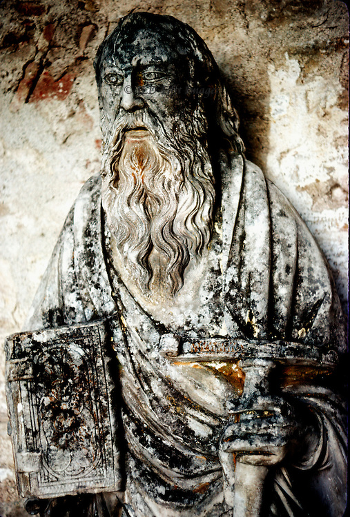 Three quarter view of the statue of a prophet in the narthex of Vezelay Abbey church: worn, stained, and dignified.