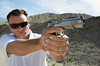 Man aiming hand gun at firing range in desert