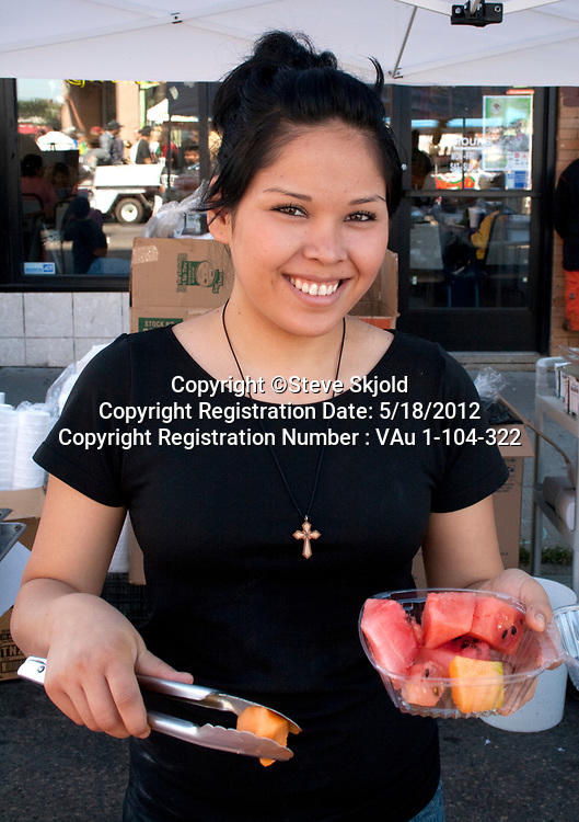 Healthy and happy Mexican American woman filling tray with fresh fruit. Mexican Independence Day Minneapolis Minnesota MN USA
