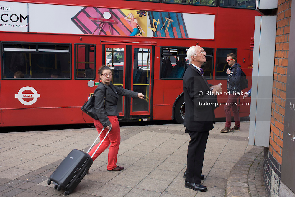 An elderly gentleman looks at a map of the city as London travellers make their way past at a Waterloo bus stop.