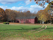 A red barn is surrounded by autumn foliage.  Classic fall New England scene captured in October in Windsor, Connecticut.