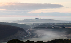 © Licensed to London News Pictures. 21/01/2014. Butser Hill, Petersfield, Hampshire, UK. A misty sunrise over the South Downs in Hampshire this morning, 21st January 2014. Cars on the A3 can be seen winding through the landscape. Photo credit : Rob Arnold/LNP