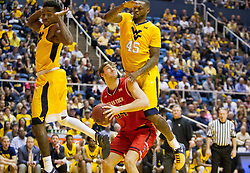 Feb 18, 2017; Morgantown, WV, USA; Texas Tech Red Raiders forward Matthew Temple (34) shoots under the basket while guarded by West Virginia Mountaineers forward Elijah Macon (45) during the first half at WVU Coliseum. Mandatory Credit: Ben Queen-USA TODAY Sports