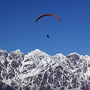 A paraglider flies above Queenstown, New Zealand with the snow capped Remarkables mountain range providing a stunning backdrop..Queenstown is nestled on the shores of the crystal clear waters of Lake Wakatipu in the Central Otago region of the South Island of New Zealand..Queenstown is New Zealand's premier tourist destination providing an abundance of year round outdoor activities for both young and old. Queenstown, Central Otago, South Island, New Zealand. 17th July 2011. Photo Tim Clayton..