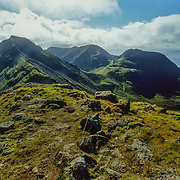 The main range of hills on Rum are called the Cuillin in the south of the island. They are rocky peaks of basalt and gabbro that are part of a core of a deeply eroded volcano that was active in the Paleogene era 66 – 23 million years ago. This view is looking towards Askival, 812 metres, and Ainshval, 778 metres, from Hallival. Hallival and Askival are formed from layered igneous rocks that accumulated at the base of a magma chamber. The chamber eventually collapsed, forming a caldera (crater). There are near vertical intrusions of basalt on the northwest coast, created by basaltic magma forcing its way into fissures in the pre-exiting rock.<br />
