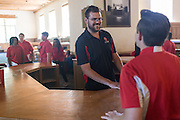 Patrick Arite talk with fellow guide Alexander Gordon during a campus tour inside Zimmerman Library on Thursday June 2, 2016. Arite and Nezzers (not pictured) are both students at the University of New Mexico and are working 15-30 hours per week giving campus tours in order to help put themselves through college. (Steven St. John for NPR)