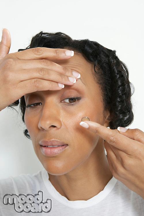 Woman applying contact lenses, studio shot