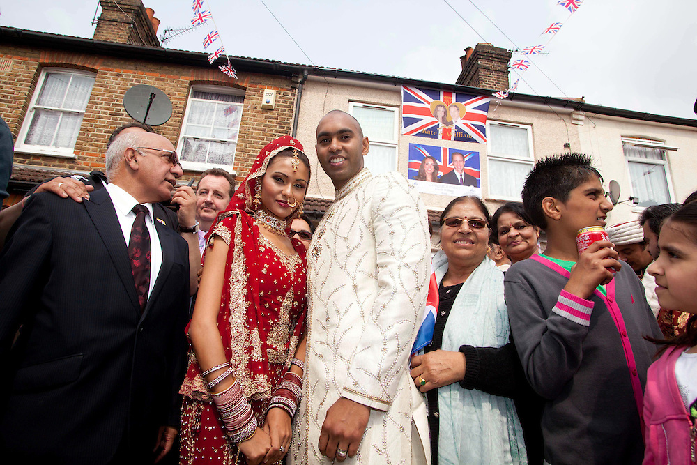 A pair of models enact their own traditional Punjabi wedding during the street party to celebrate the Royal wedding. Outside the former home to Kate Middleton's Grandmother, the local community came out in their thousands to celebrate in Punjabi style, Clarence Street, Southall.