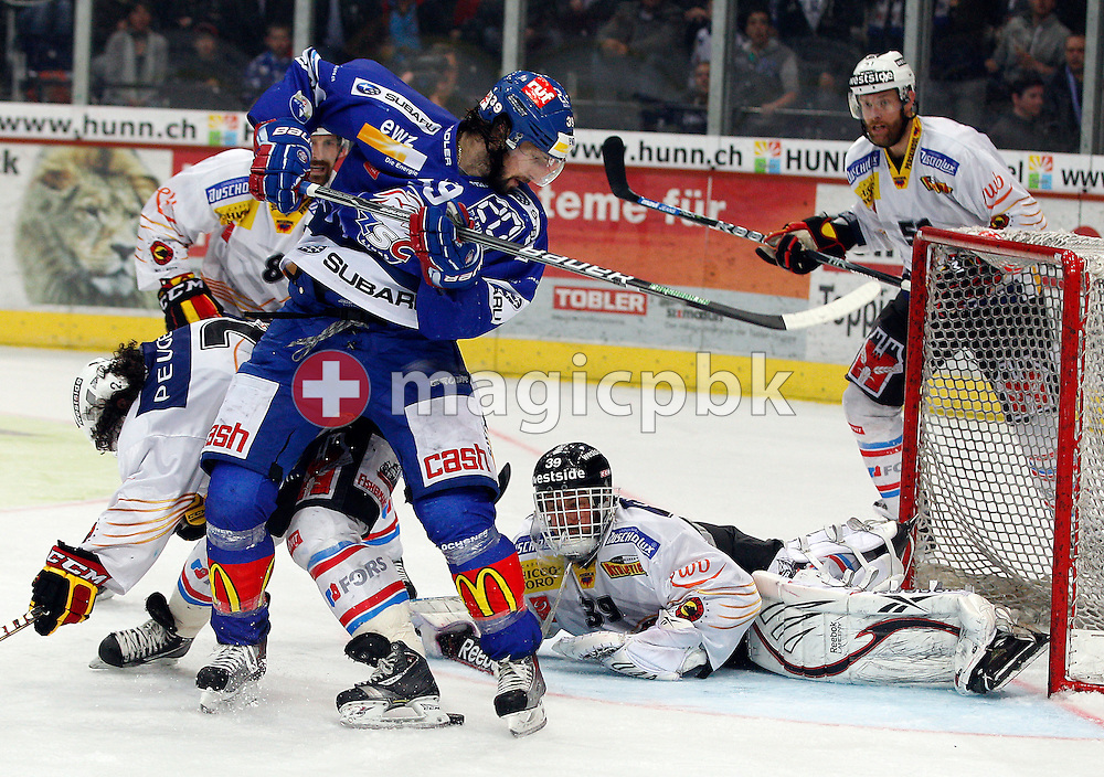 ZSC Lions forward Mark Bastl (front) fights for the puck against SC Bern defender Beat Gerber (L) and goaltender Marco Buehrer during ice hockey game two of the Swiss National League A (Season 2011-2012) Playoff Final between ZSC Lions (ZSC) and SC Bern (SCB) held at the Hallenstadion in Zurich, Switzerland, Thursday, April 5, 2012. (Photo by Patrick B. Kraemer / MAGICPBK)