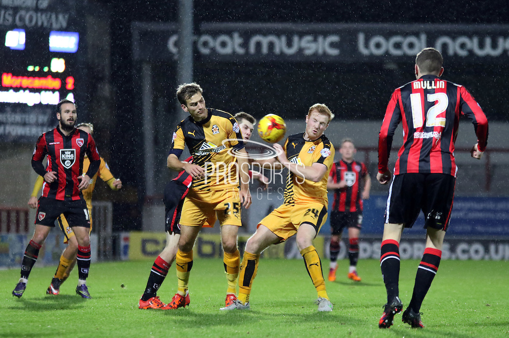 Conor Newton and Mickey Demetriou challenge during the Sky Bet League 2 match between Morecambe and Cambridge United at the Globe Arena, Morecambe, England on 24 November 2015. Photo by Pete Burns.