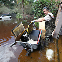 Ed Perez removes waterlogged belongings from his garage in the Ashborough community near Summerville on Thursday after floodwater from the Ashley River receded by about 1 foot. (ANDREW KNAPP/STAFF)