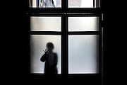 silhouetted woman entering a dark space seen through frosted glass