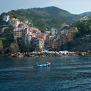 Two local fisherman drive their small blue fishing boat in nothern Italy's Riveria located in the bay of Riomaggiore Cinque Terre region in western Italy.