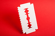 Big white ice scraper  shaped as razor blade with one sharp edge and one toothed edge isolated on red background, tilted and with smooth shadows.