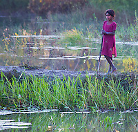 Young swineherd girl standing by a wetland in the Terai region of Nepal