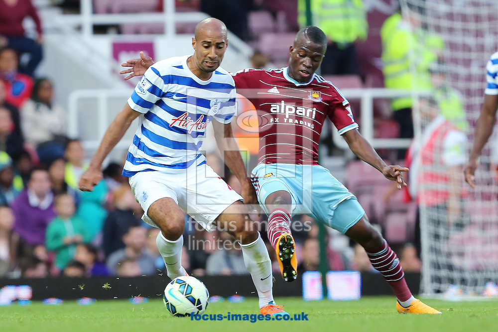 Enner Valencia of West Ham United and Karl Henry of Queens Park Rangers during the Barclays Premier League match at the Boleyn Ground, London<br /> Picture by Richard Calver/Focus Images Ltd +447792 981244<br /> 05/10/2014