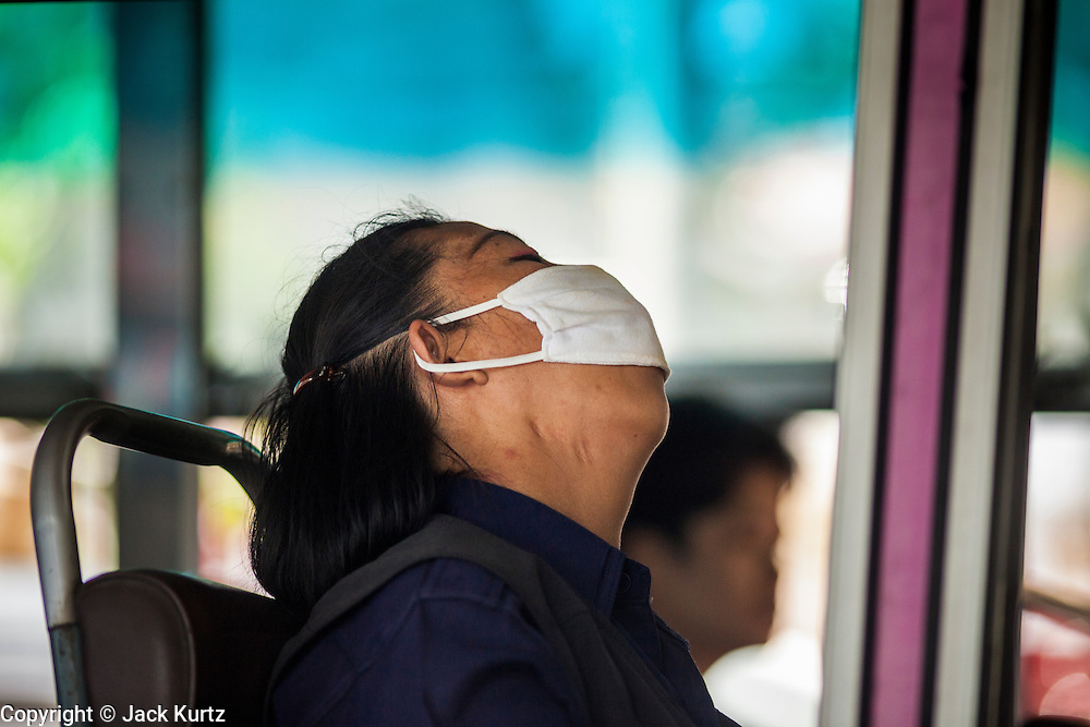 "20 MAY 2104 - BANGKOK, THAILAND:  A woman sleeps on a Bangkok bus after the Thai army declared martial law. The Thai Army declared martial law throughout Thailand in response to growing political tensions between anti-government protests led by Suthep Thaugsuban and pro-government protests led by the ""Red Shirts"" who support ousted Prime Minister Yingluck Shinawatra. Despite the declaration of martial law, daily life went on in Bangkok in a normal fashion. There were small isolated protests against martial law, which some Thais called a coup, but there was no violence.  PHOTO BY JACK KURTZ"
