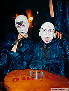 Two guys wearing white masks and blue velvet capes/gowns, one man sticking out his tongue, Ibiza, 2000
