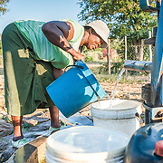 CAPTION: In the early morning, Locodia collects water from a pre-existing borehole pump. It tends to be the jobs of women and children to collect water for their households twice a day; these pumps are very heavy and difficult for them to use. LOCATION: Mawoneke Village, Chivi District, Masvingo Province, Zimbabwe. INDIVIDUAL(S) PHOTOGRAPHED: Locodia Mudinyi.