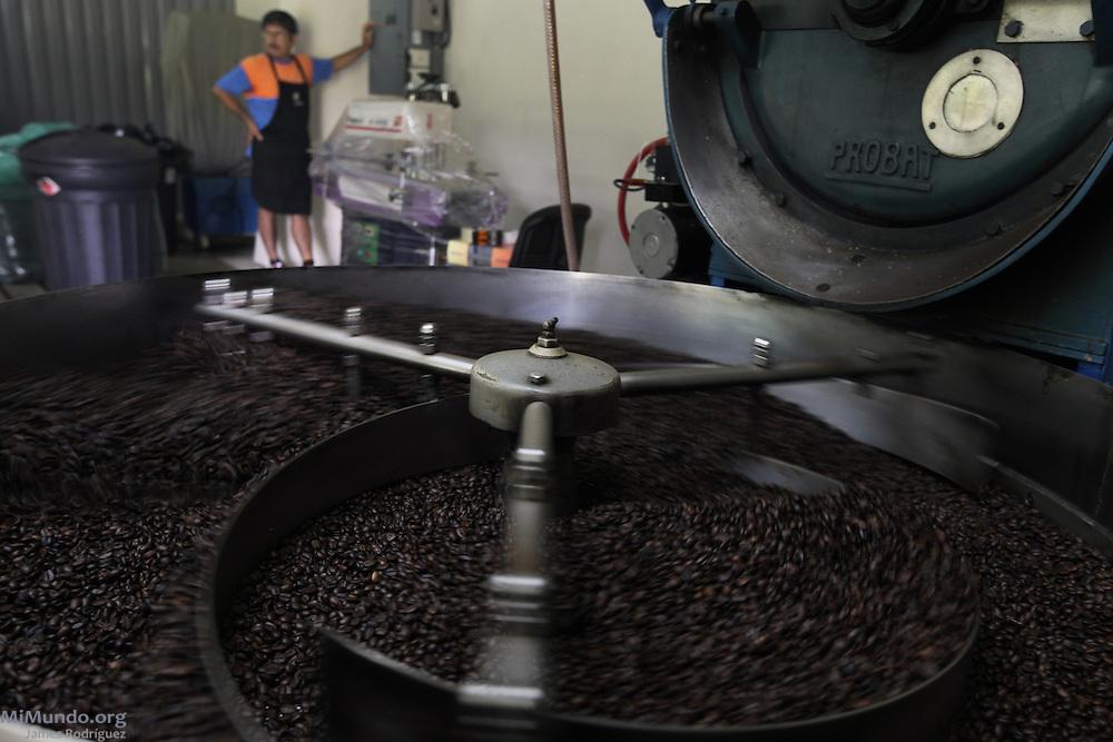 José Cerdas Chaves turns on a switch as coffee beans roast. COOCAFE, Tilarán, Guanacaste, Costa Rica. August 22, 2012.