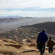 'Attitude at Altitude' Football in Potosi, Bolivia'..Miners head to work in the infamous hill Cerro Rico which overlooks the mining town of Potosi, Bolivia, 12th May 2010. Photo Tim Clayton..'Attitude at Altitude' Football in Potosi, Bolivia'..The Calvario players greet the final whistle with joyous celebration, high fives and bear hugs the players are sprayed with local Potosina beer after a monumental 3-1 victory over arch rivals Galpes S.C. in the Liga Deportiva San Cristobal. The Cup Final, high in the hills over Potosi. Bolivia, is a scene familiar to many small local football leagues around the world, only this time the game isn't played on grass but a rock hard earth pitch amongst gravel and boulders and white lines that are as straight as a witches nose, The hard surface resembles the earth from Cerro Rico the huge mountain that overlooks the town. .. Sitting at 4,090M (13,420 Feet) above sea level the small mining community of Potosi, Bolivia is one of the highest cities in the world by elevation and sits 'sky high' in the hills of the land locked nation. ..Overlooking the city is the infamous mountain, Cerro Rico (rich mountain), a mountain conceived to be made of silver ore. It was the major supplier of silver for the spanish empire and has been mined since 1546, according to records 45,000 tons of pure silver were mined from Cerro Rico between 1556 and 1783, 9000 tons of which went to the Spanish Monarchy. The mountain produced fabulous wealth and became one of the largest and wealthiest cities in Latin America. The Extraordinary riches of Potosi were featured in Maguel de Cervantes famous novel 'Don Quixote'. One theory holds that the mint mark of Potosi, the letters PTSI superimposed on one another is the origin of the dollar sign...Today mainly zinc, lead, tin and small quantities of silver are extracted from the mine by over 100 co operatives and private mining companies who still mine the mountain in poor working conditions, children are still used