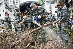 August 27, 2017 - Macao, China - Officers and soldiers from the People's Liberation Army (PLA) Garrison in Macao clean downed trees from a street after typhoons Hato and Pakhar hit back to back in southern China. Pakhar, the 14th typhoon of the year, struck Macao on Sunday, days after Typhoon Hato caused damage in the region. (Credit Image: © Cheong Kam Ka/Xinhua via ZUMA Wire)