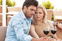 Young couple having red wine at outdoor restaurant