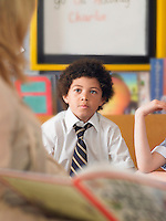 Elementary schoolboy listening to teacher read in classroom