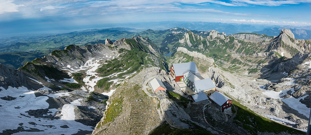 Berggasthaus Alter Säntis is perched dramatically atop Säntis (2502 m / 8218 feet), the highest peak of the Alpstein range and the Appenzell Alps, located in northeast Switzerland, Europe. On right is Altmann peak (2435m), second highest of the Appenzell Alps. Shared by three cantons, Säntis can be reached easily via aerial tramway (Luftseilbahn) from Schwägalp, or with effort via wonderful trails, to see vast mountain views across six countries: Switzerland, Germany, Austria, Liechtenstein, France and Italy. We highly recommend staying overnight on top of Säntis as we did at Berggasthaus Alter Säntis, a fifth-generation family-run mountain inn since 1850, offering modern private double and dormitory lodging with good food and magnificent views. From where we joined it at Rotsteinpass, the spectacular, rocky Lisengrat trail to Säntis is rigged with safety cables in case of icy or wet conditions (and can be scary for those with fear of heights). In rainy weather the next day, we took the easy tram down to Schwägalp instead of hiking to Ebenalp. The Appenzell Alps rise between Lake Walen and Lake Constance. This image was stitched from multiple overlapping photos.