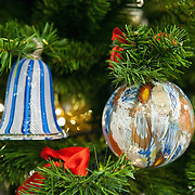 VENICE, ITALY - DECEMBER 14: Murano Glass Christmas baubles hand made at Eugenio Ferri & C. glass factory hang on a Christmas tree on December 14, 2010 in Venice, Italy. The production of glass baubles is an highly skilled process,with a variety of styles, often with the inclusion of gold and silver foil.