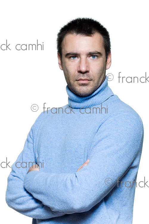 studio portrait on isolated background of a stubble man serious