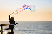 Women Playing with a Bubble Maker off of the Huntington Beach Pier