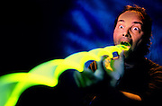 Man swallowing long glowing spiral.Black light
