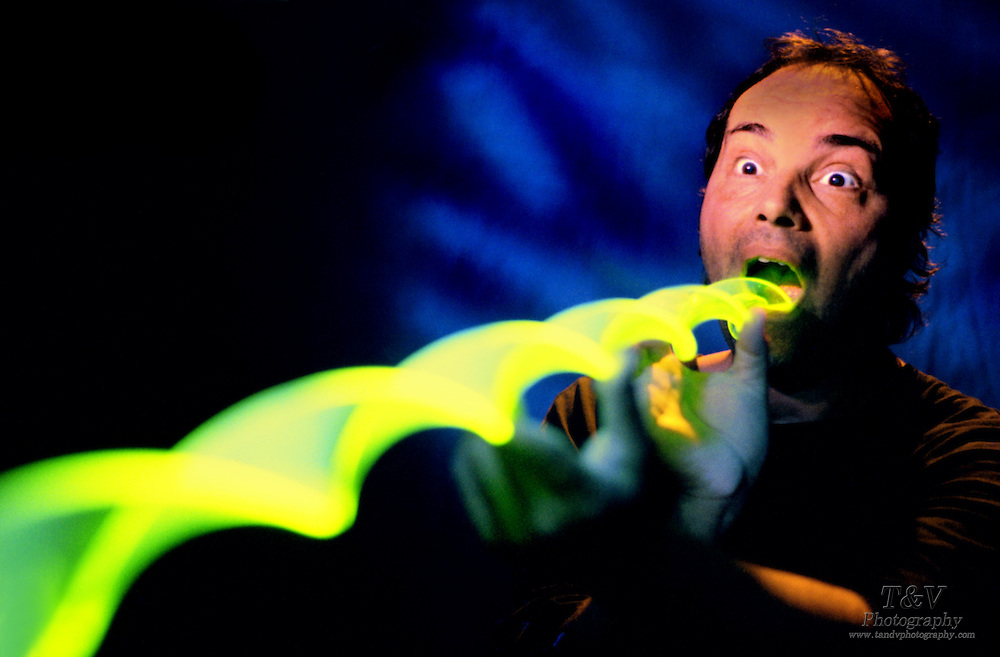 Man swallowing long glowing spiral.Black light