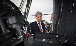 © London News Pictures. 11/07/2012. Farnborough, UK. Philip Hammond being shown around a Wildcat  helicopter. Defence Secretary Philip Hammond officially receiving first Wildcat helicopters from AgustaWestland on behalf of the armed forces on day three of the Farnborough International Airshow, in Farnborough, Hampshire, UK on July 9, 2012. FIA is a seven-day international trade fair for the aerospace industry which is held every two years at Farnborough Airport . Photo credit: Ben Cawthra/LNP.