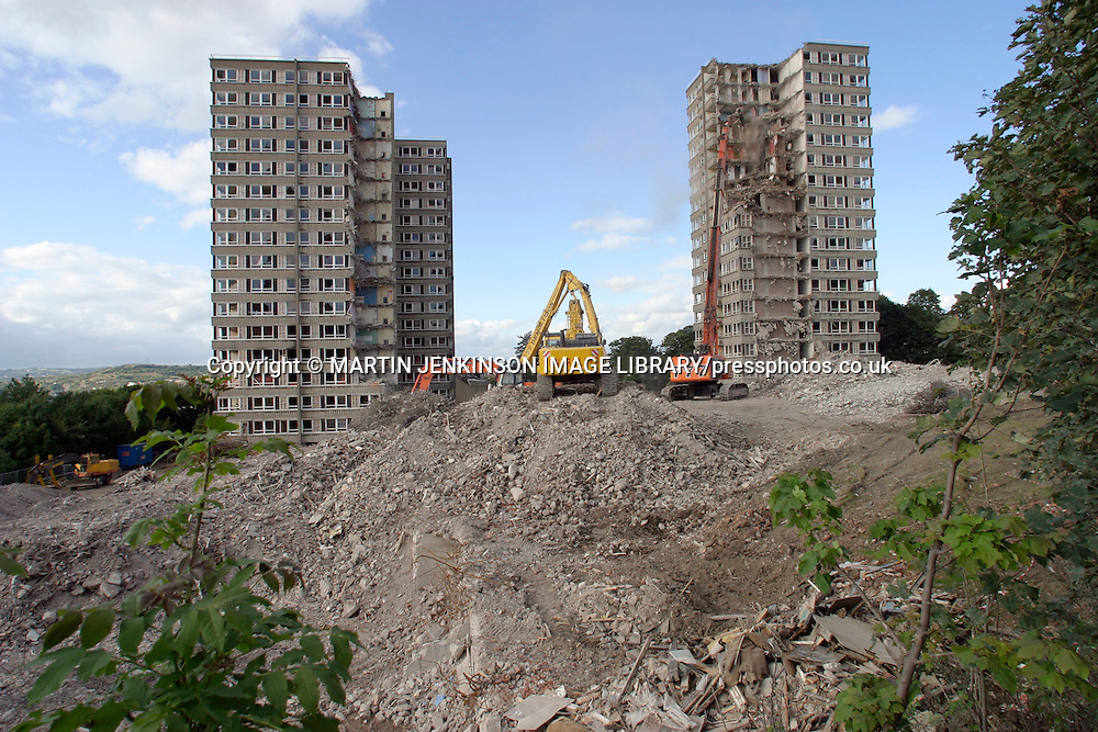 Demolition of high rise flats using a hydraulic jaw to cut through steel reinforced concrete....
