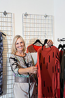 Portrait of a happy senior woman browsing in fashion boutique