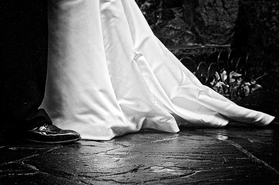 The bride's wedding gown trail and the groom's polished leather shoes.