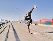 A rapper dances on a lonely dock while handstands
