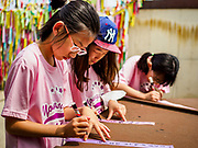 09 JUNE 2018 - IMJINGAK, PAJU, SOUTH KOREA: South Korean school children write inscriptions on prayer flags they will hang on a fence near the northernmost point on the South Korean side of the Korean DMZ in Imjingak. Imjingak is a park and greenspace in South Korea that is farthest north most people can go without military authorization. The park is on the south bank of Imjin River, which separates South Korea from North Korea and is close the industrial park in Kaesong, North Korea that South and North Korea have jointly operated.     PHOTO BY JACK KURTZ
