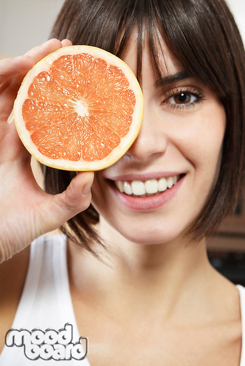 Woman holding half of grapefruit in front of face portrait close up