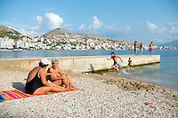 In the waning days of summer two women sit on the beach and converse as children play and others stand on the pier in Sarande (Saranda), Albania