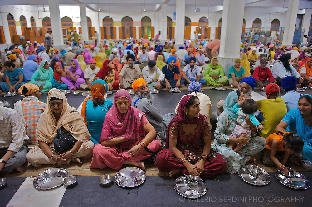 Sitting along regular lines on jute carpets, people waits to be served. Anyone is invited to share the meal in community. Sikhs rejects any discrimination on any base, food is offered for free to everyone.