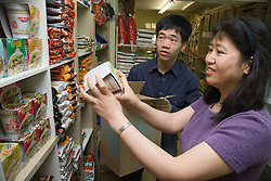 Shop workers stacking shelves an oriental food stall,