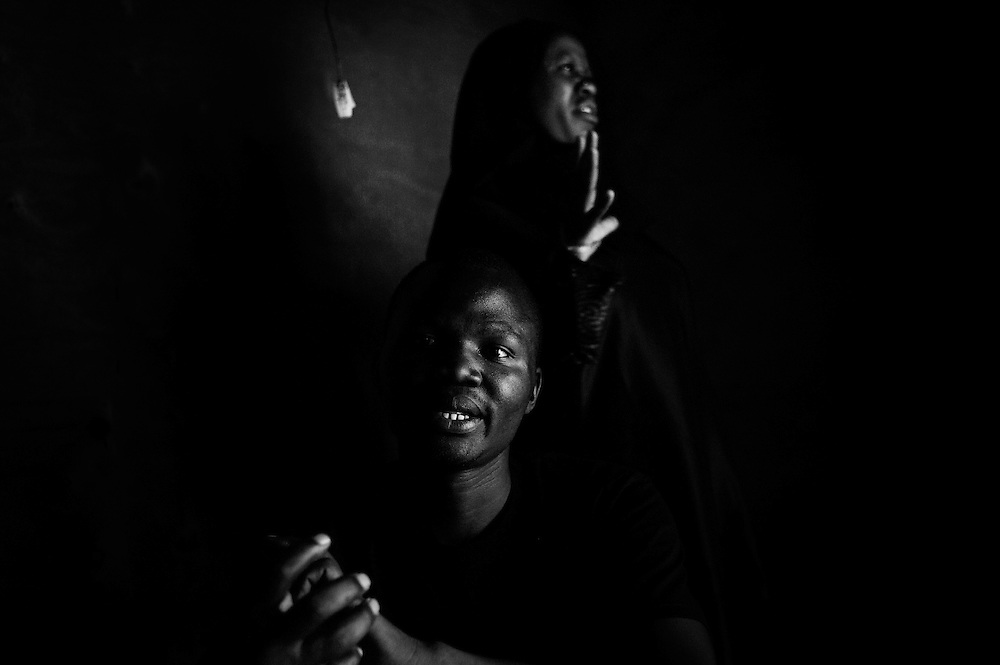 """NAIROBI, KENYA - AUGUST 17, 2011: Moses Omondi, 30, gathers with friend and Chief Campaign Manager, Joan Limbala, (back) in Kibera. Omondi serves as an elected Youth Leader at the sublocation level for youth in Kisumundogo, one of Kibera's many villages. With Limbala's help, Omondi hopes to be elected to the position of County Representative for Makina County in 2012. If elected, Omondi will represent Kibera as a new constituency before the governor, alongside two to four other representatives.<br /> <br /> Various grassroots initiatives led by youth have begun to improve the quality of life for those living in the direst of conditions, and young people of different tribes are using gardening, waste removal, education and athletics to encourage their peers toward a self-respecting and self-sustaining community. Termed """"youth groups"""" on the street, these initiatives could represent the future of long-term socioeconomic development in Kenya while laying the groundwork for a more peaceful election in 2013. During the post-election violence of 2007 and 2008, impoverished youth in Kenya were routinely bribed by the nation's political elite to carry out acts of violence in their communities. Idleness among the youth, combined with the nation's history of tribal rivalries, were cited as a key factors to the violence, culminating in the deaths of over 1,200 Kenyans and the displacement of over 600,000. Since the violence, many youth have begun to seize active roles in the reform of their nation. In 2010 United States Ambassador Michael Ranneberger said he sensed """"a sea change of attitude"""" among youths, """"a tidal wave below the surface. The youth have woken up."""""""