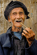An old man smoking pipe in Tiantouzhai village, Dragon's backbone Rice terraces, China