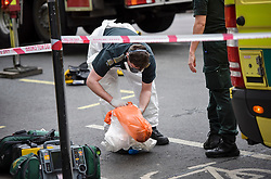 © Licensed to London News Pictures. 01/04/2020. London, UK. Ambulance workers decontaminate at the scene of an incident involving all emergency services where a suspected COVID-19 case was isolatedand removed from home. Uxbridge Road in Shepherd's Bush was closed for an hour as ambulance, fire brigade and police attended, extracting the patient by crane from a three story apartment building in West London. PPE (personal protective equipment) was in evidence, with the fire brigade using full facerespirators normally reserved for firefighting. A police officercommented the Metropolitan police force are issued only with rubber gloves. Ambulance workers decontaminated the scene and reusable equipment before moving on.  Photo credit: Guilhem Baker/LNP